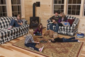 family playing games in log cabin interior