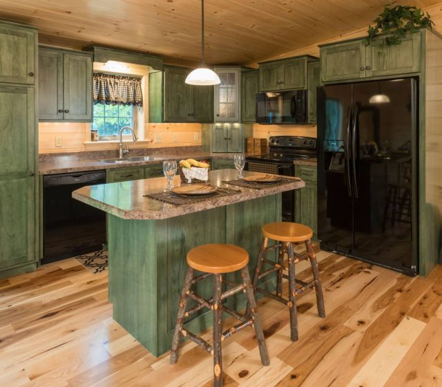 green wooden cabinets in log cabin kitchen