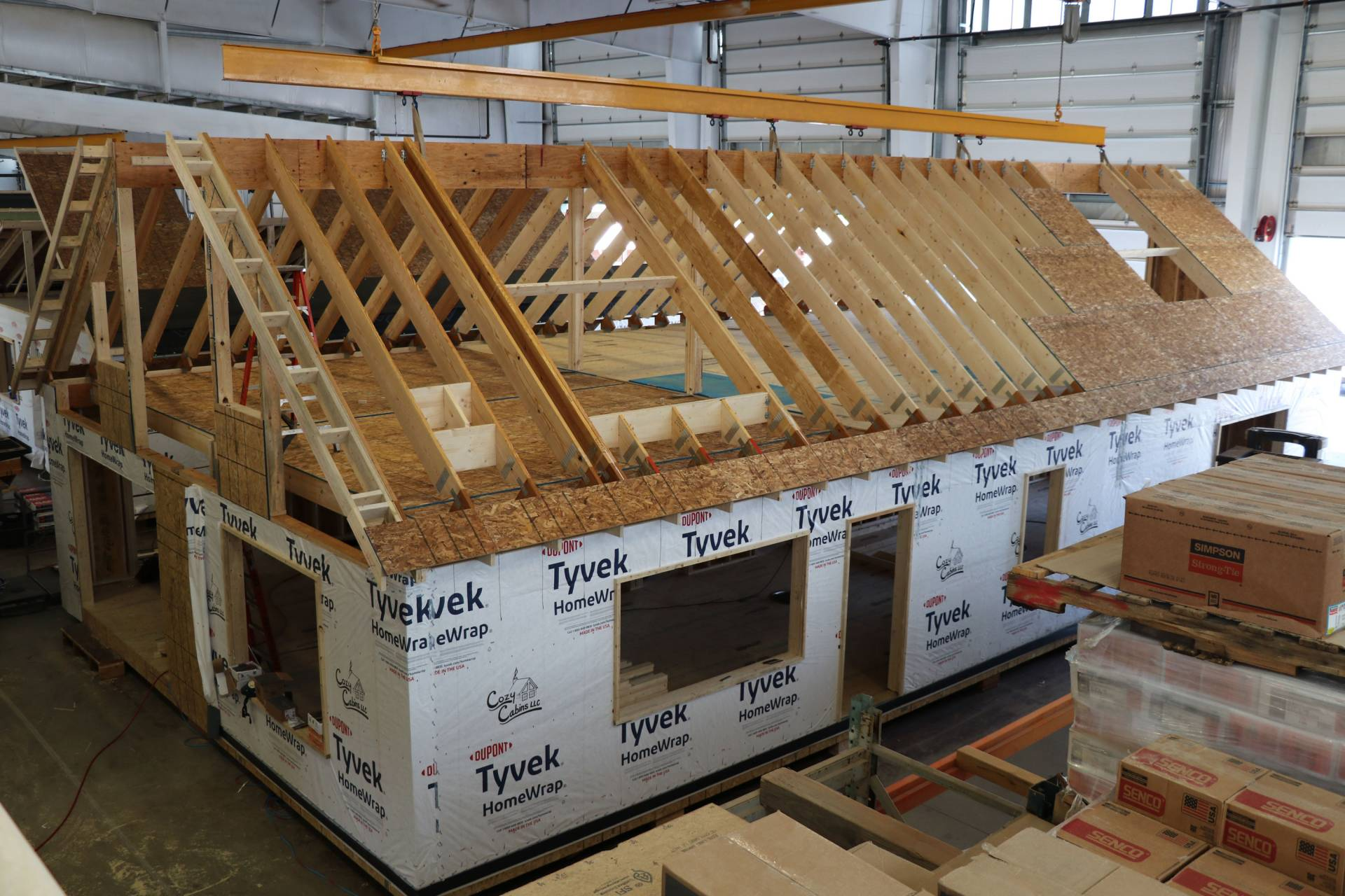 roof being put on modular log home in Lancaster warehouse