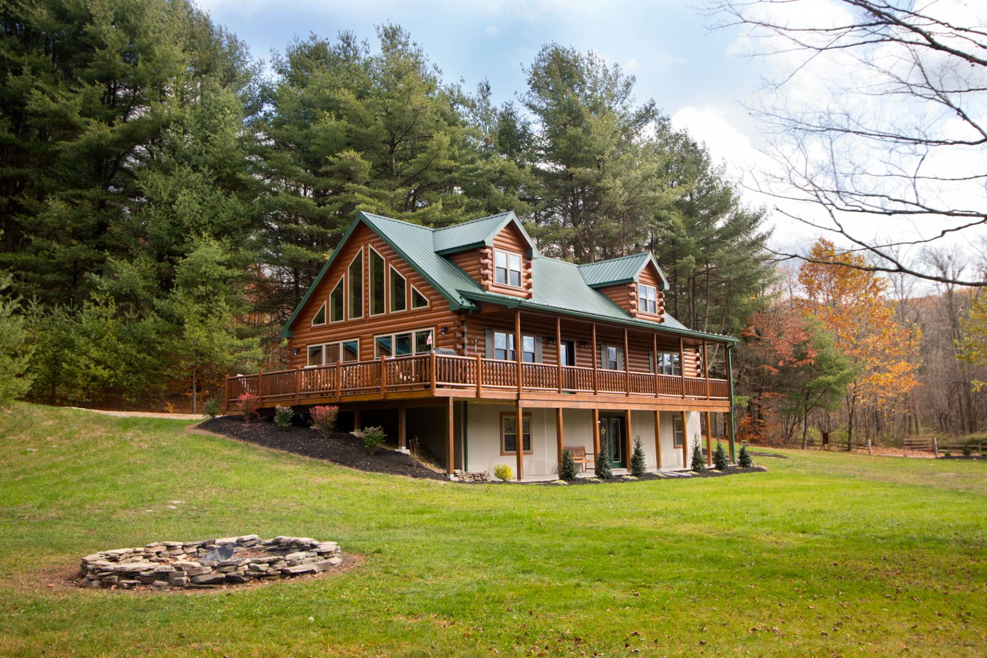 multi story log home with full wrap around porch
