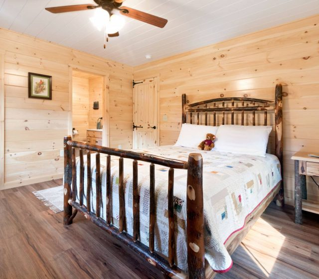 log cabin bedroom with white pine siding