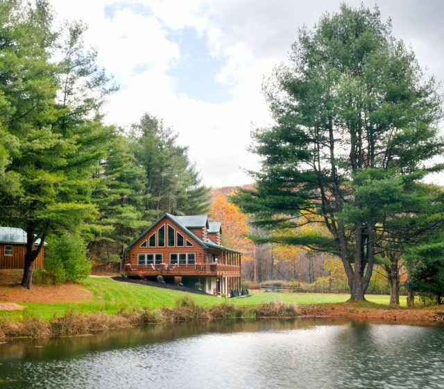 beautiful log cabin besides river in the forest